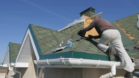 telha : soft roof of shingles. Repair of the roof of a residential house. installation of soft tiles. partial replacement of the damaged roof. Dot repair. Nailing roofing material to the surface of the sloping roof. Hand hammer strikes the hat metal nails. Stock Footage