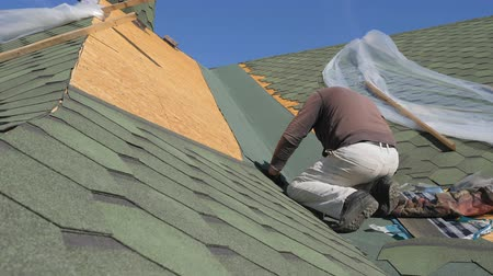 dekarz : soft roof of shingles. Repair of the roof of a residential house. installation of soft tiles. partial replacement of the damaged roof. Dot repair. carpenter throws a hammer up and catches it. Worker juggles on top. Nailing roofing material to the surface