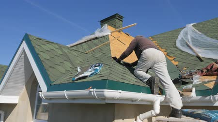 fotografia : soft roof of shingles. Repair of the roof of a residential house. installation of soft tiles. partial replacement of the damaged roof. Dot repair. Nailing roofing material to the surface of the sloping roof. fitting and installation of roofing material