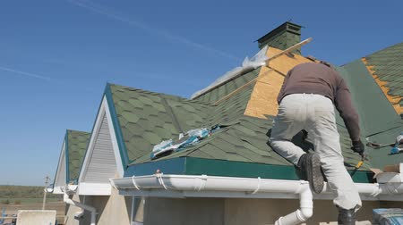dekarz : soft roof of shingles. Repair of the roof of a residential house. installation of soft tiles. partial replacement of the damaged roof. Dot repair. Nailing roofing material to the surface of the sloping roof. Hand hammer strikes the hat metal nails. Wideo