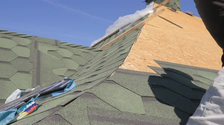 dekarz : soft roof of shingles. Repair of the roof of a residential house. installation of soft tiles. partial replacement of the damaged roof. Dot repair. master cuts off excess roofing material with scissors. Wideo