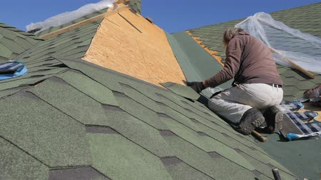 macro fotografia : soft roof of shingles. Repair of the roof of a residential house. installation of soft tiles. partial replacement of the damaged roof. Dot repair. Nailing roofing material to the surface of the sloping roof. Hand hammer strikes the hat metal nails.Master