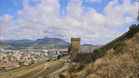 vista de cima : Mountains against the blue sky with white clouds. Cirrus clouds run across the blue sky. Part of the fortress wall on the background of the city located in the valley. Figures tourists moving along the wall of an ancient fortress on the mountain trails.