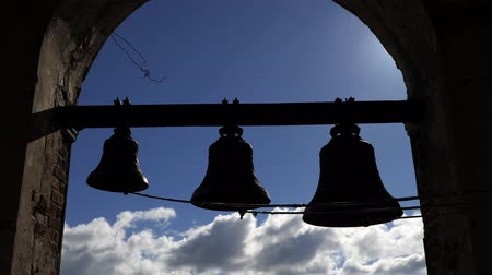 hoje : bells on the background of blue sky with clouds. Bells of various sizes hang in a brick arch at high altitude.