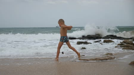 raging : Boy at the raging sea. Boy in swimming trunks is trying to keep his balance while standing on a stone in the strong gusts of wind. Stock Footage