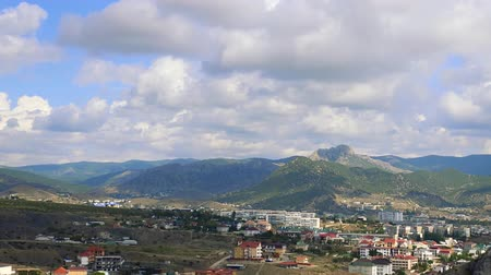 krym : Genoese fortress, Sudak, Crimea. Mountains against the blue sky with white clouds. Cirrus clouds run across the blue sky. Top view of the city in the mountains, the buildings and the road with passing cars. Motion in the frame. Beautiful alluring landscap