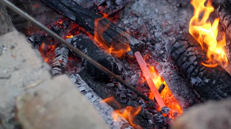 felvidéki : blacksmith works metal. Craftsman, the Highlander on private smithy in the village. Burning logs in the blacksmiths furnace. Removing the preform from scorching hot crucible, using the poker. Slow motion