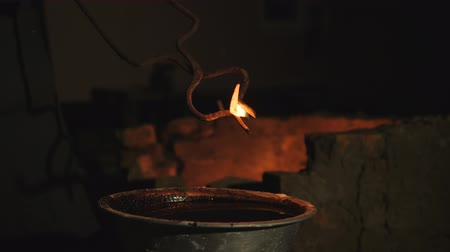 antiquado : blacksmith works metal. Craftsman, the Highlander on private smithy in the village. hardening of metal products. Bathing hot product in a container with cold oil. Oil flashes open fire. Slow motion Stock Footage