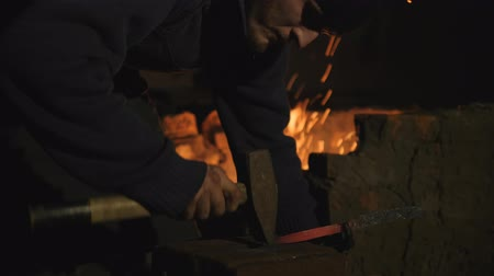 felvidéki : Young blacksmith works metal. Craftsman, the Highlander on private smithy in the village. shaping sharp dagger. red-hot billet in processing. Slow motion
