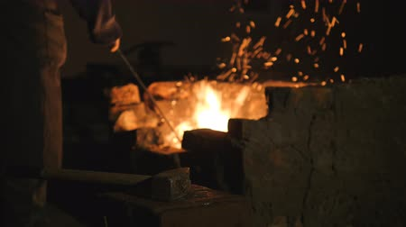marreta : blacksmith works metal. Craftsman, the Highlander on private smithy in the village. Craftsman interferes with embers in the furnace. Hands are dressed in fire resistant mittens. Sparks fly apart. 2000, 1041, DIN. On the blacksmiths forge lies a sledgehamm