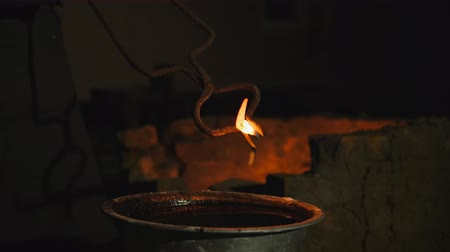 felvidéki : blacksmith works metal. Craftsman, the Highlander on private smithy in the village. hardening of metal products. Bathing hot product in a container with cold oil. Oil flashes open fire. Slow motion Stock mozgókép