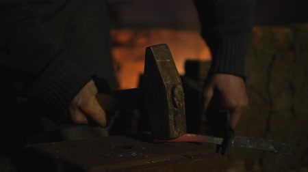 топор : blacksmith works metal. Craftsman, the Highlander on private smithy in the village. Shaping the metal billet. Craftsman sledgehammer beats on the workpiece knife. Sparks fly in different directions. Hot rod puts on the anvil, the master hits him with a sl