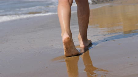 ślady stóp : Child goes along the surf. Childrens feet on the background of waves. sea water washes away the footprint Wideo