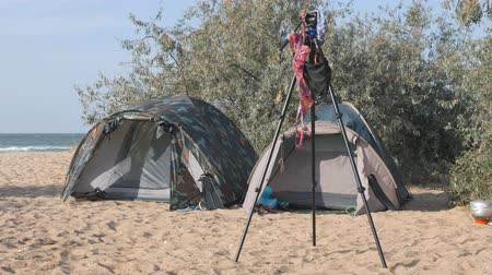 штатив : Tourist camp, tents and a car are in the tourist parking lot. On the tripod of the photographer hanging swimsuit moving gusts of wind
