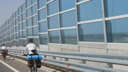 абсорбент : Cyclist rides along the protective screen of the motorway