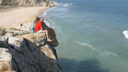 rozbíjení : Man sits on the edge of a cliff. Waves wash the sandy shore. Ridge is broken on the rocks