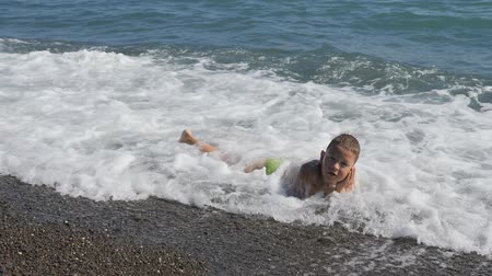пробуждение : boy in the sea surf. Child covers the wave. The boy lies in the sea on the rocks. Water lulls the baby. Стоковые видеозаписи