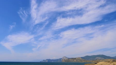 snow on grass : Mountains against the blue sky with white clouds. Cirrus clouds run across the blue sky. The best views of the coast. Beautiful view of the sea. best video of the mountainous coast Stock Footage