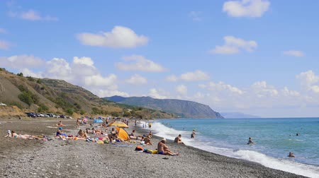 krym : September 6, 2018, Morskoye village, Crimea, editorial. People in bathing suits on a pebble beach by the sea. Mountains against the blue sky with white clouds. Cirrus clouds run across the blue sky. The best views of the coast. Beautiful view of the sea.
