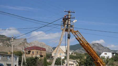ricostruzione : Electricians at the height of mounting wires. Rise on height by means of the machine of a tower