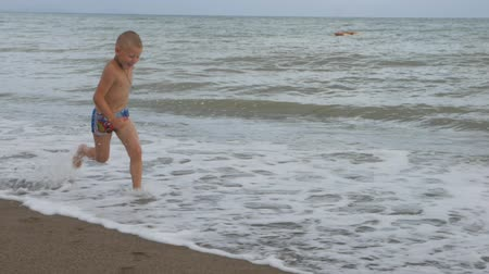 подробный : Tanned Boy runs along the coast on the golden sand. slow motion