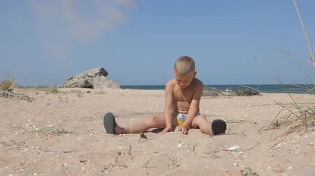 head over : Blond boy sitting on the sandy beach throws up over his head the yellow sand.