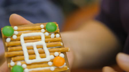 glassa : Family traditions. Decoration gingerbread house. Preparing for the holiday of Christmas Filmati Stock