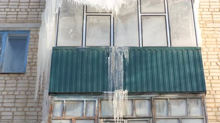 melt : Winter. Icicles hanging from the roof and balconies of an apartment building Stock Footage