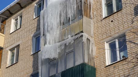 sincelo : Winter. Icicles hanging from the roof and balconies of an apartment building Stock Footage