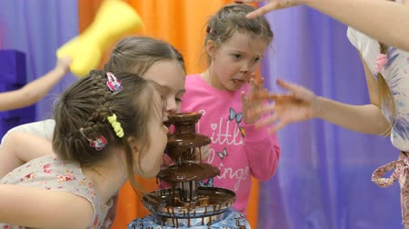 liquid : Childrens playroom. Children eat chocolate from a chocolate fountain.