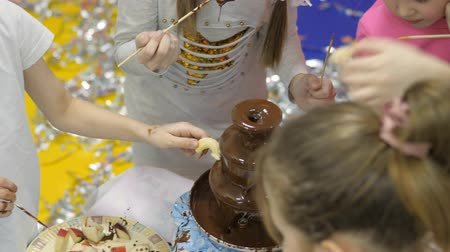 fontain : Childrens playroom. Children eat chocolate from a chocolate fountain.