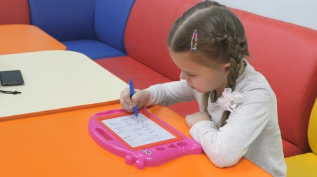 piada : Childrens playroom. Studio entertainment for young children. Cute little girl pains on blackboard special pen. Stock Footage