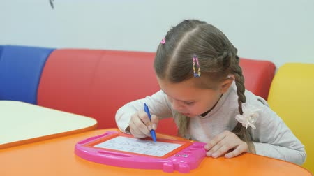 piada : Childrens playroom. Studio entertainment for young children. Cute little girl pains on blackboard special pen. Vídeos