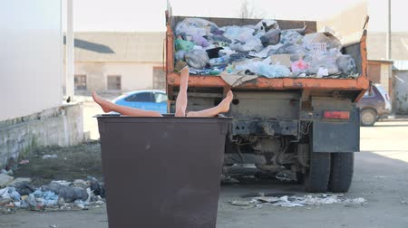 atmak : Legs sticking out of the garbage can. The truck body is filled with garbage.