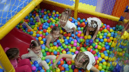 multicor : Childrens playroom. Children play in a dry basin filled with plastic colored balls.