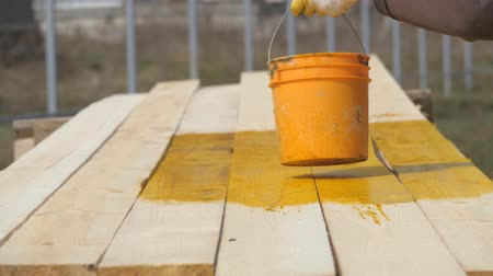 furnér : Covering wooden planks with antiseptic. Paint brush wooden surface of wood. Orange paint bucket is on the table. Stock mozgókép
