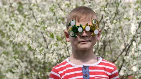 ložisko : Spinner on the glasses is spinning. Fun on the street. A spinning toy on a funny face. A white flower of the cherry tree.