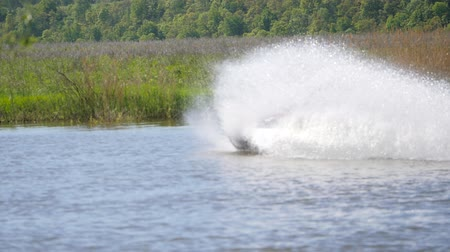 激しい : Jet ski on the river. Splashes fly apart.