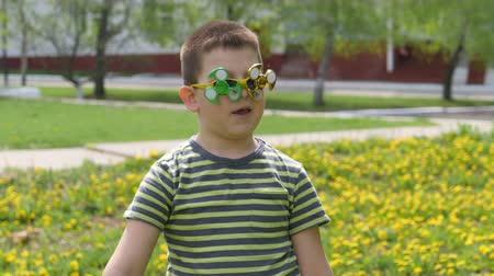 fidget spinner : Spinner on the glasses is spinning. Fun on the street. Boy on a background of yellow flowers, dandelions.