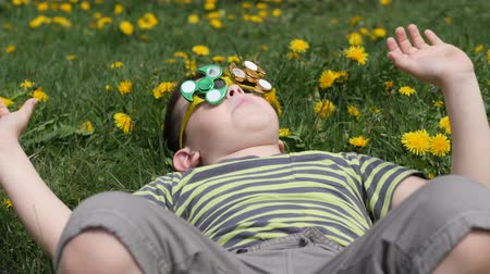 ložisko : Spinner on the glasses is spinning. Fun on the street. Boy on a background of yellow flowers, dandelions.