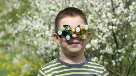 fad : Spinner on the glasses is spinning. Fun on the street. A child on the background of blossoming white flowers of cherry tree. Stock Footage
