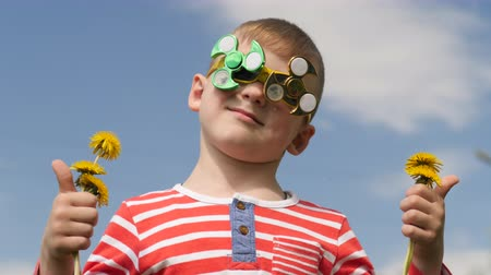 fidget spinner : Spinner on the glasses is spinning. Fun on the street. Baby boy against the blue sky.