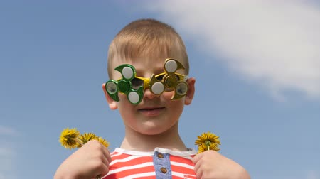 stationary : Spinner on the glasses is spinning. Fun on the street. Baby boy against the blue sky.