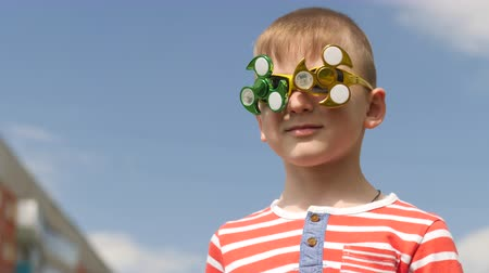 fad : Spinner on the glasses is spinning. Fun on the street. Baby boy against the blue sky.