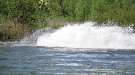 моторная лодка : Jet ski on the river. Splashes fly apart. A man on a water bike splits the water.