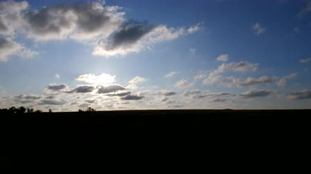 Sunrise in the steppe. The sun shines through the clouds. Cirrus clouds are running across the blue sky.