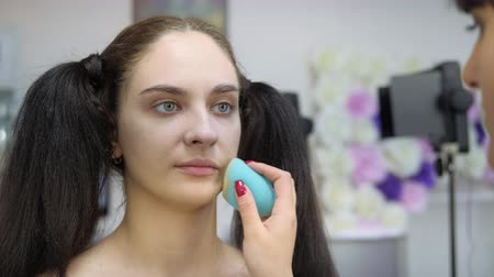 Face makeup. Alignment of the skin texture with a sponge and powder.