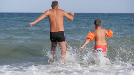 Beach summer vacation. A man and a child run into the raging sea to dive.