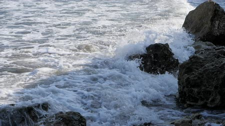 Waves break on the shore. Waves break on the rocks.