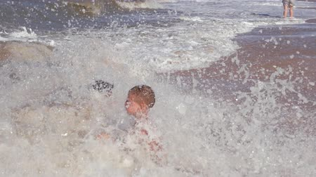 Beach summer vacation. Children in the raging waves. Stock Footage